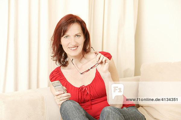 Middle-aged redheaded woman sitting on sofa holding her glasses and a mobile phone