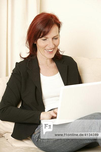 Frau im mittleren Alter mit Laptop auf dem Sofa