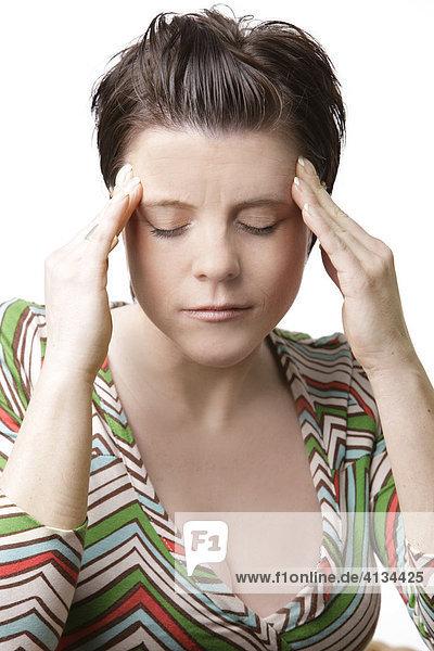 Frau fasst sich an die Schläfen  Augen geschlossen