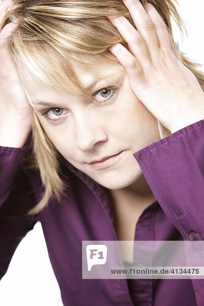 Blonde woman wearing a purple shirt  her head leaning on her hands