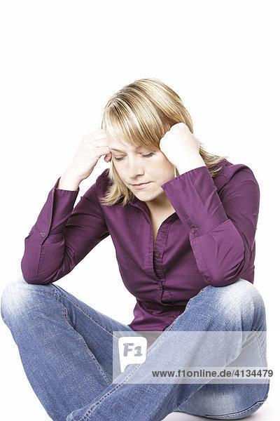 Blonde Frau im lila Hemd  stützt den Kopf mit den Händen  Augen geschlossen