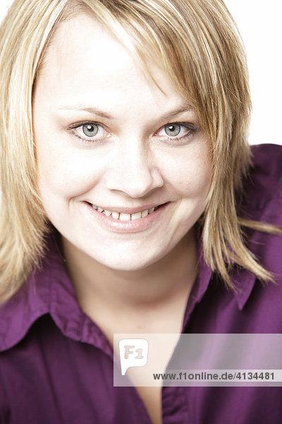 Blonde woman wearing a purple shirt  smiling