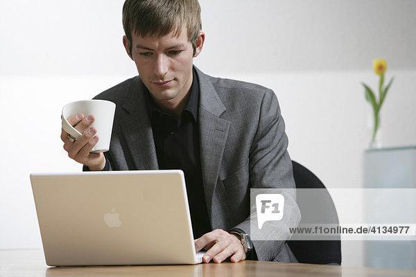 DEU  Bundesrepublik Deutschland : Junger Mann arbeitet an einen Laptop Computer  Apple