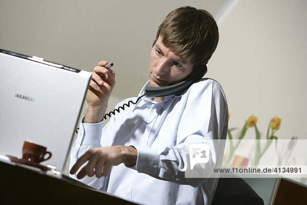 DEU  Germany : Young man is working at his laptop computer  on the phone