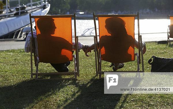 Paar  Mann und Frau liegen in Liegestuhl in der Sonne  Silhoutte
