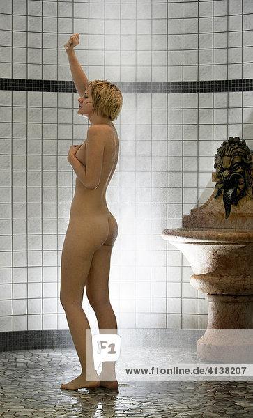 AUT  Österreich  Neustift-Milders  Stubaital: Wellness. Junge Frau in einem Spa  Wellnessbereich. Abkuehlen nach der Sauna. Kalt duschen. Wellnesshotel Milderer Hof.
