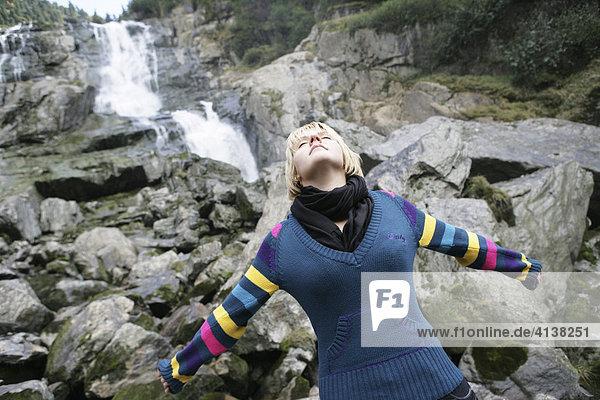 AUT  Oesterreich  Neustift  Stubaital: Alpen- Wellness. Gesundes inhalieren von feinem Wasserspray an einem Wasserfall. Das fein zerstaeubte Wasser in der Naehe des Wasserfalls soll eine positive Wirkung auf die Atemorgane haben.
