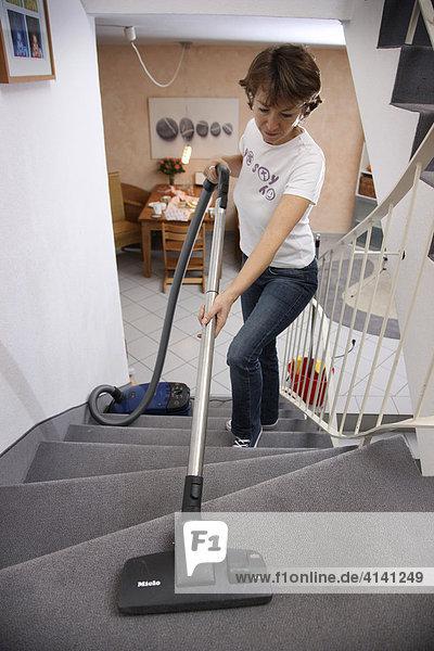 Haushalt  Frau beim Staubsaugen in einer Wohnung