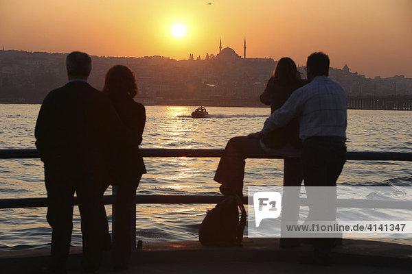 Stadtpanorama  Touristen  bei Sonnenuntergang am Goldenen Horn  von der Galatabrücke aus gesehen  Istanbul  Türkei