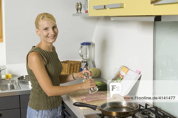 Young woman prepares schnitzel