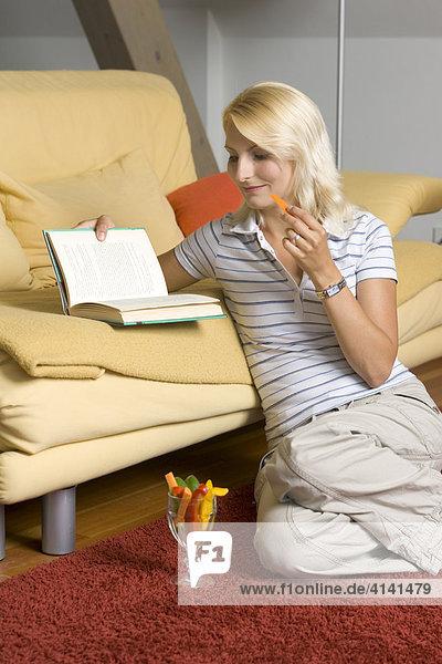 Junge Frau isst beim Lesen