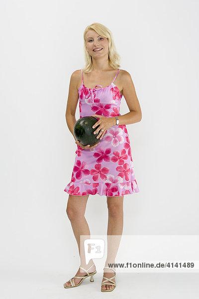 Junge Frau hält Melone