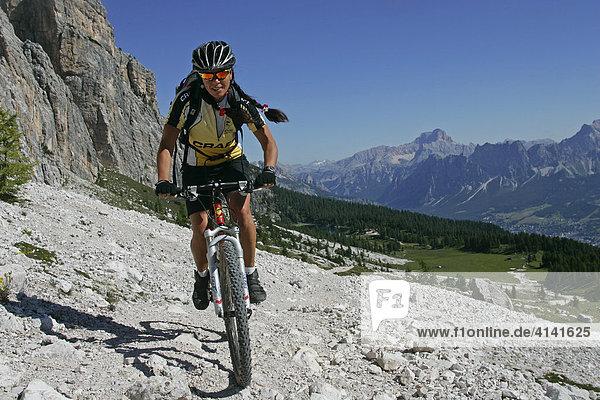 Mountainbike-Fahrerin an der Cima d' Ambrizzola mit Lago di Fedara und Croda Rossa im Hintergrund  Dolomiten  Italien