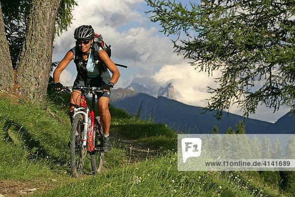 Mountainbikerin am Karerpass  mit Pala-Gruppe im Hintergrund  Dolomiten  Italien