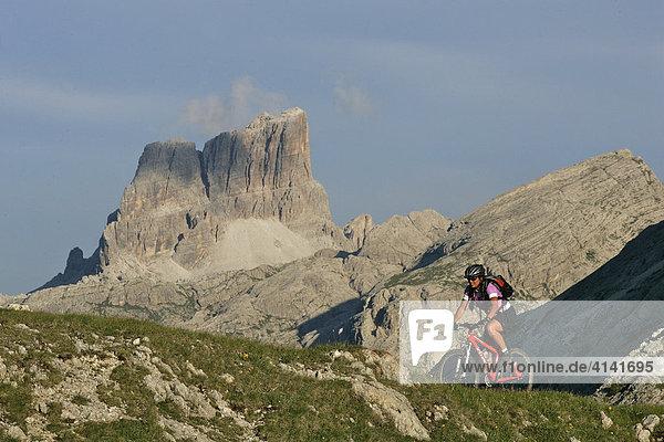 Mountainbikerin am Valparola Pass  mit Grande Torre im Hintergrund  Dolomiten  Italien