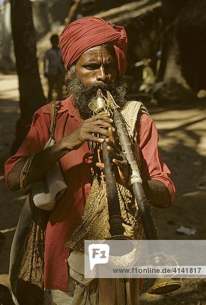 Mann bläst auf zwei shenai (indische Oboe)  Goa  Indien
