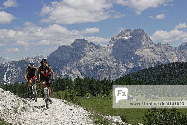 Mountainbike-Fahrerinnen an der Croda da Lago  mit Sorapis-Massiv  Dolomiten  Italien