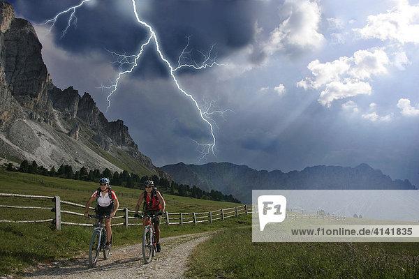 Mountainbike-Fahrerinnen im Gewitter mit Blitz am Peitlerkofel  Dolomiten  Italien