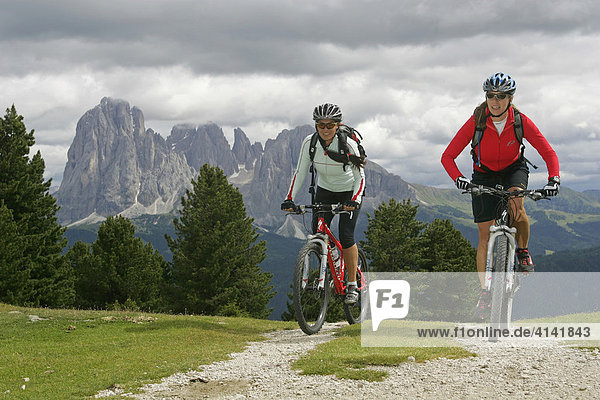 Mountainbike-Fahrerinnen mit Langkofel und Plattkofel im Hintergrund  Dolomiten  Italien