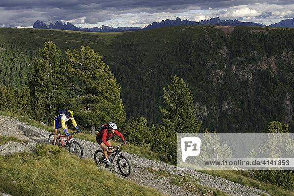 Mountainbiker und -bikerin an der Gedrum Alm mit Blick auf die Dolomiten  Sarntal  Südtirol  Italien