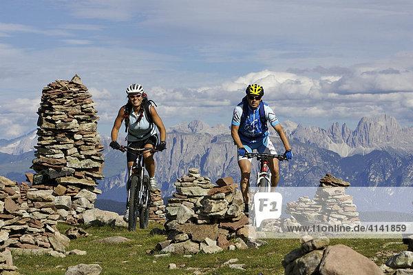 Mountainbiker und -bikerin bei den Stoanernen Mandlen auf der Hohen Reisch mit Dolomiten im Hintergrund  Südtirol  Italien  Europa