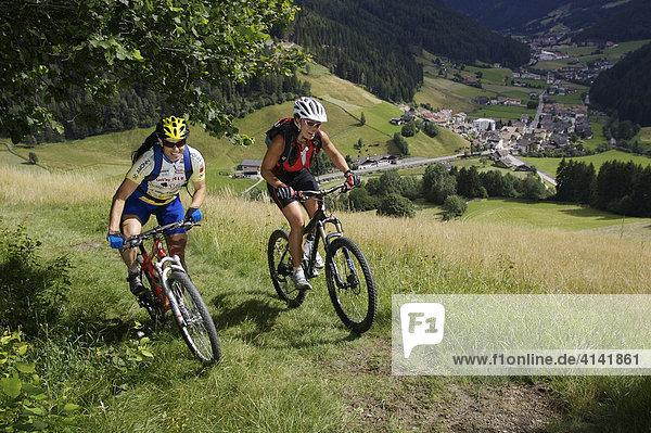 Mountainbiker und -bikerin am Messner-Hof mit Blick auf Astfeld und St. Valentin bei Sarnthein  Sarntal  Südtirol  Italien