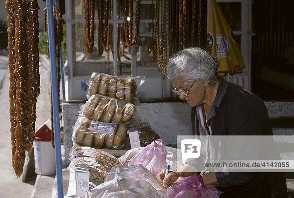 Frau in einem Laden  wo Soutzouko  eine süße Spezialität  Ketten aus Mandeln und Traubensaft  verkauft wird  Lania  Zypern