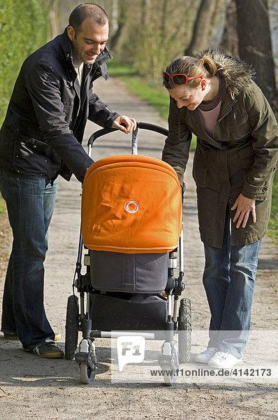 Junge Eltern mit Kinderwagen
