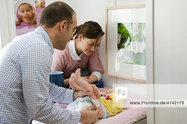 Junge Eltern am Wickeltisch  Vater wickelt das Baby