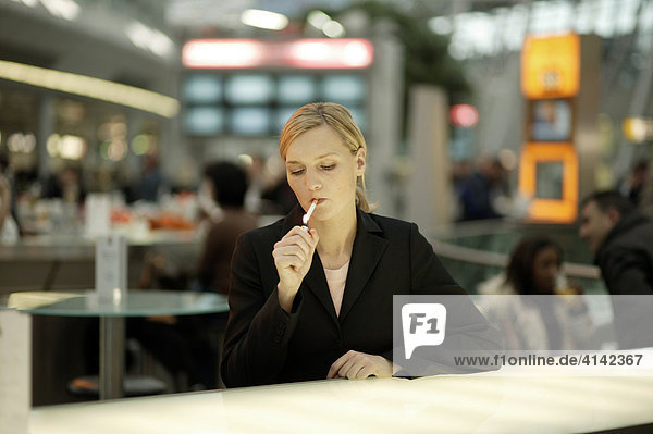 Junge Frau raucht in Airport-CafÈ