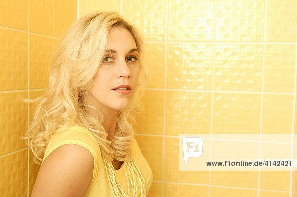 Junge blonde Frau im gelben Kleid vor gelbem Hintergrund