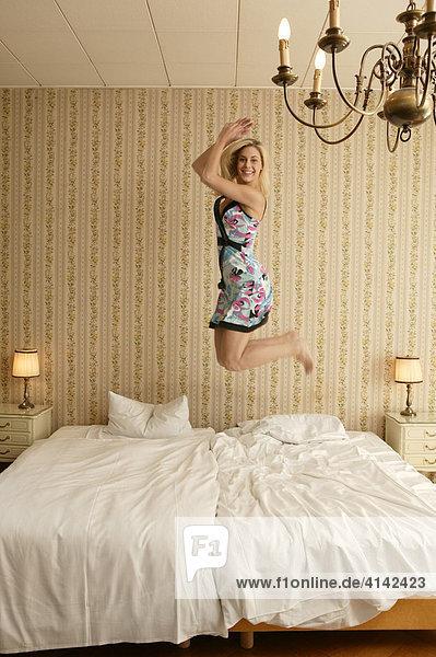 Junge blond Frau im bunten Kleid springt auf dem Bett in die Luft