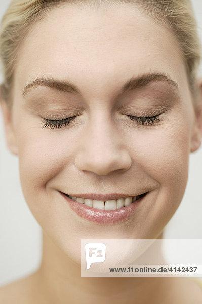 Junge  blonde Frau mit geschlossenen Augen lächelt  Gesicht in Nahaufnahme