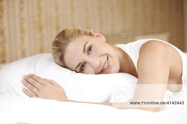 Junge  blonde Frau liegt auf Kissen
