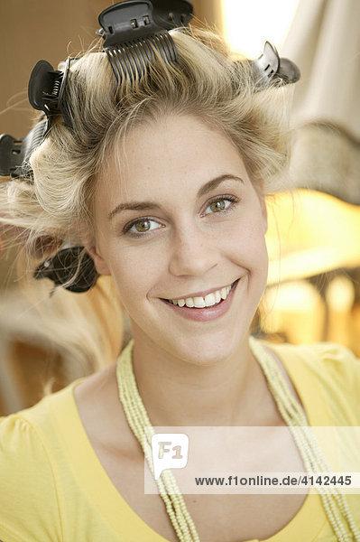 Blondes Fotomodell mit Lockenwicklern  lächelt in Kamera