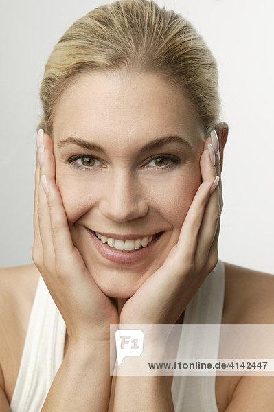 Junge  blonde Frau mit aufgestützten Händen lächelt