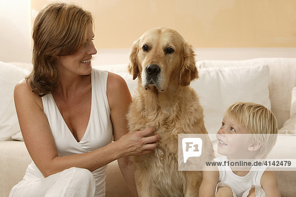 Frau mit Hund und Sohn vor dem Sofa