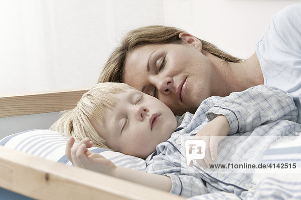 Mother and son sleeping in bed