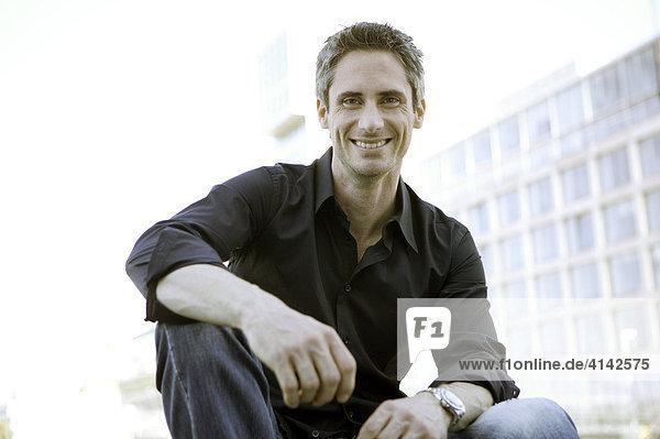 Junger Mann im schwarzen Hemd vor Hochhaus