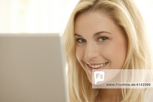 Junge blonde Frau am Laptop  lächelt