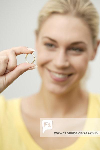 Junge  blonde Frau begutachtet lächelnd Ehering  Schärfe auf Ring