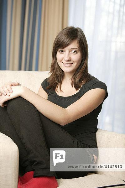 17-jähriges Mädchen mit roten Socken sitzt auf Sofa und lächelt