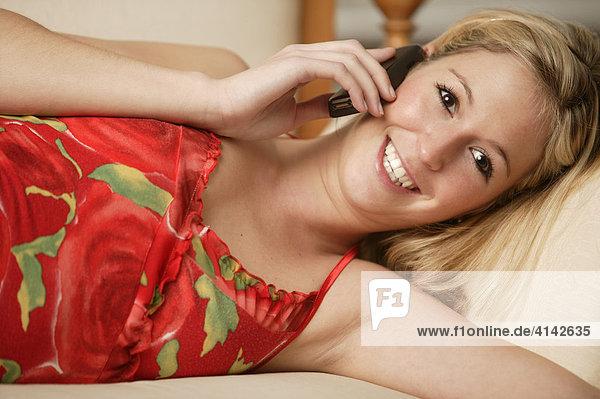 Junge Frau im roten Kleid liegt auf Sofa und telefoniert
