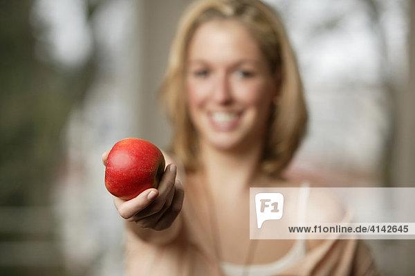Junge  blonde Frau präsentiert roten Apfel  lächelt. Frau unscharf  selektive Schärfe