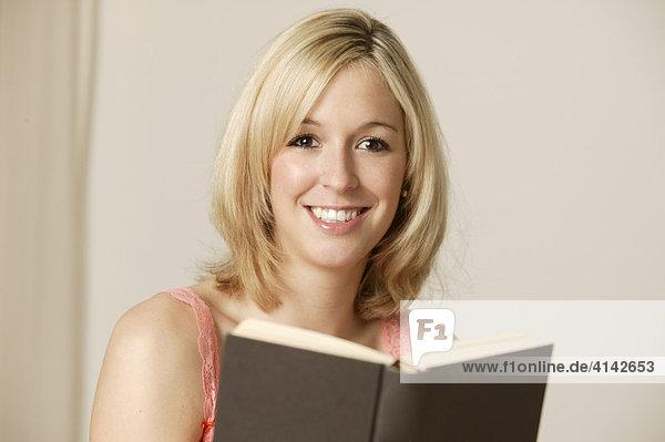 Junge  blonde Frau mit Buch  lächelt