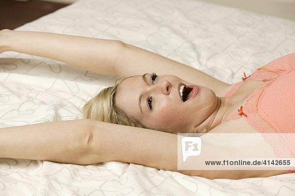 Junge  blonde Frau streckt sich und gähnt auf dem Bett
