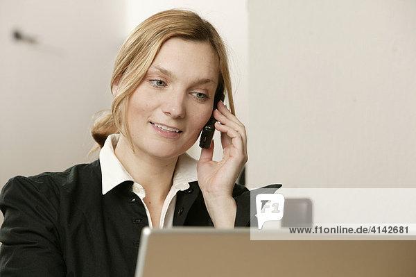 Blonde Frau mit Laptop  telefoniert
