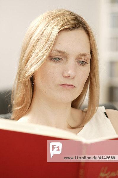Blonde Frau liest rotes Buch