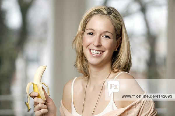 Junge  blonde Frau mit Banane  lächelt