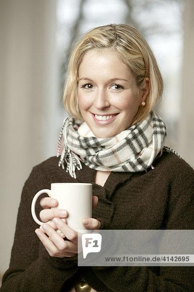 Junge Frau im dunklen Pullover mit Schal  mit Tasse  lächelt